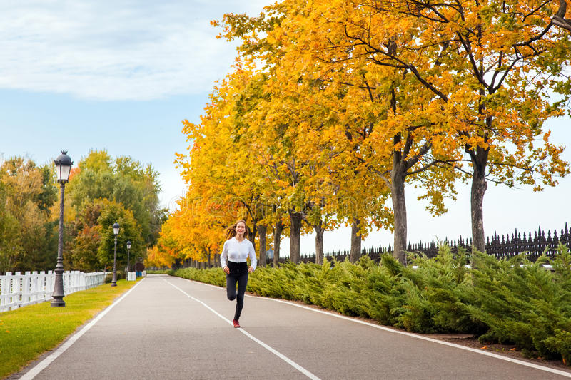 Woman running in autumn forest. Young adult girl jogging in fall stock photos