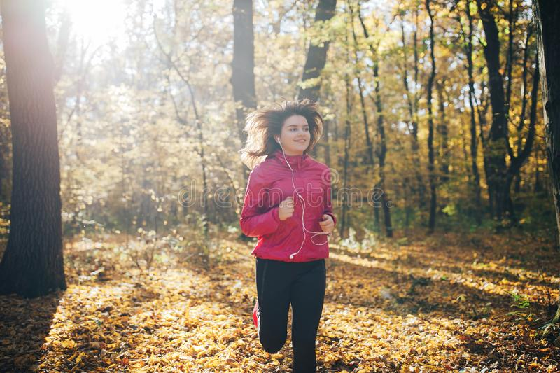 Woman running during autumn morning forest royalty free stock photo