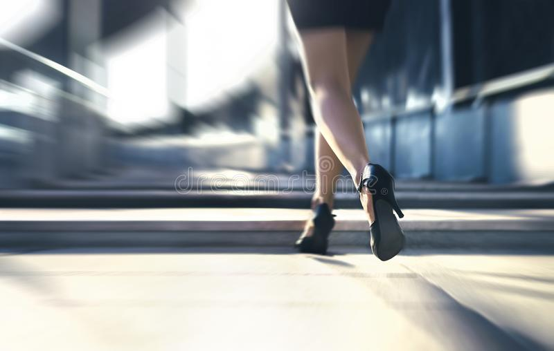 Woman running away or walking fast with high heels in city street. Busy business person in hurry. Late from work or stress fast. royalty free stock photos