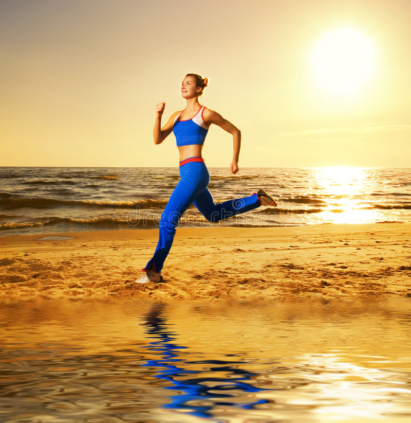 Woman running on a beach. Beautiful young woman running on a beach at sunset