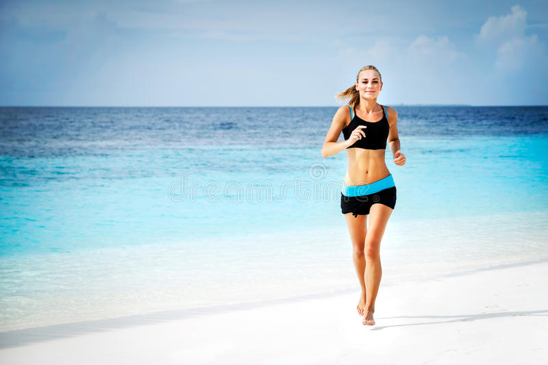 Woman running on the beach. Beautiful sportive woman running along beautiful sandy beach, healthy lifestyle, enjoying active summer vacation near the sea stock photos