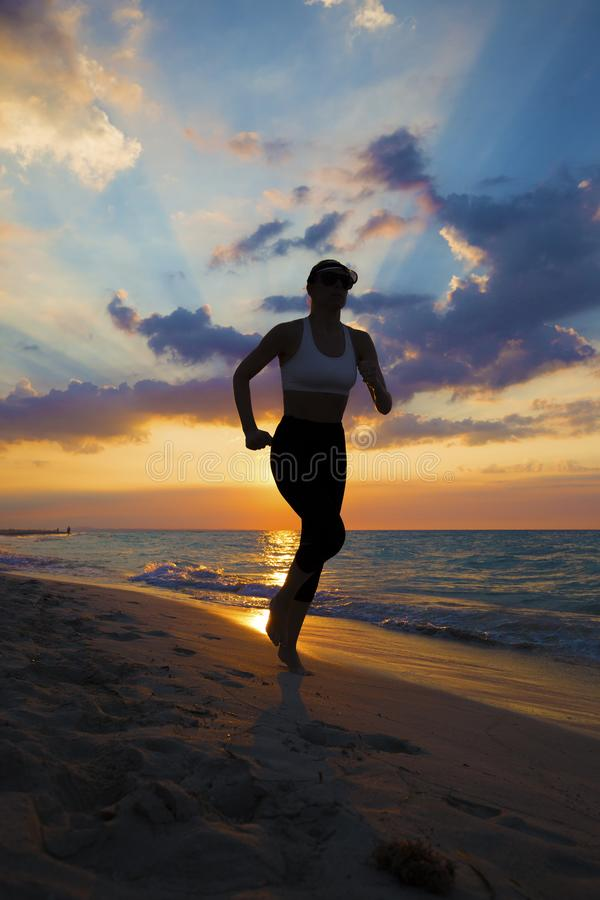 Woman running on the beach during sunset. stock image