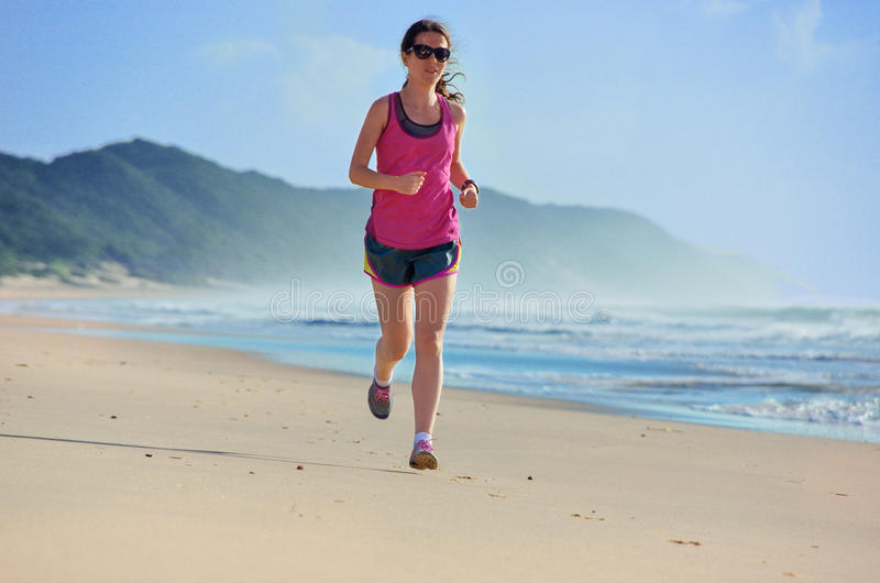 Woman running on beach, girl runner jogging outdoors. Woman running on beach, beautiful girl runner jogging outdoors, training for marathon, exercising and stock photo
