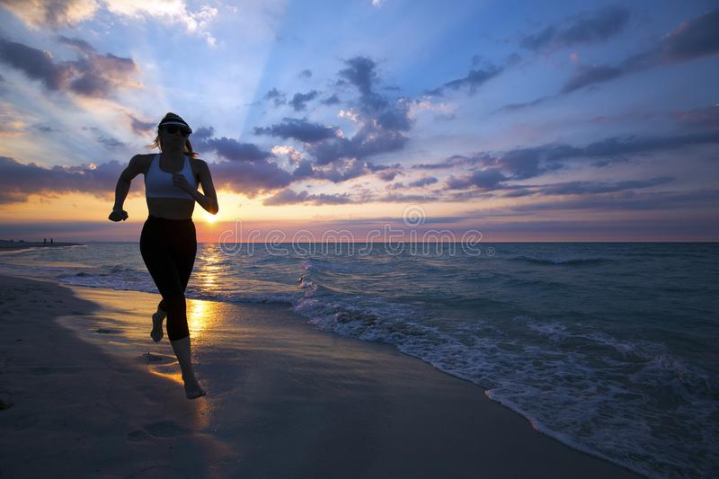 Woman running on the beach during sunset. stock photo