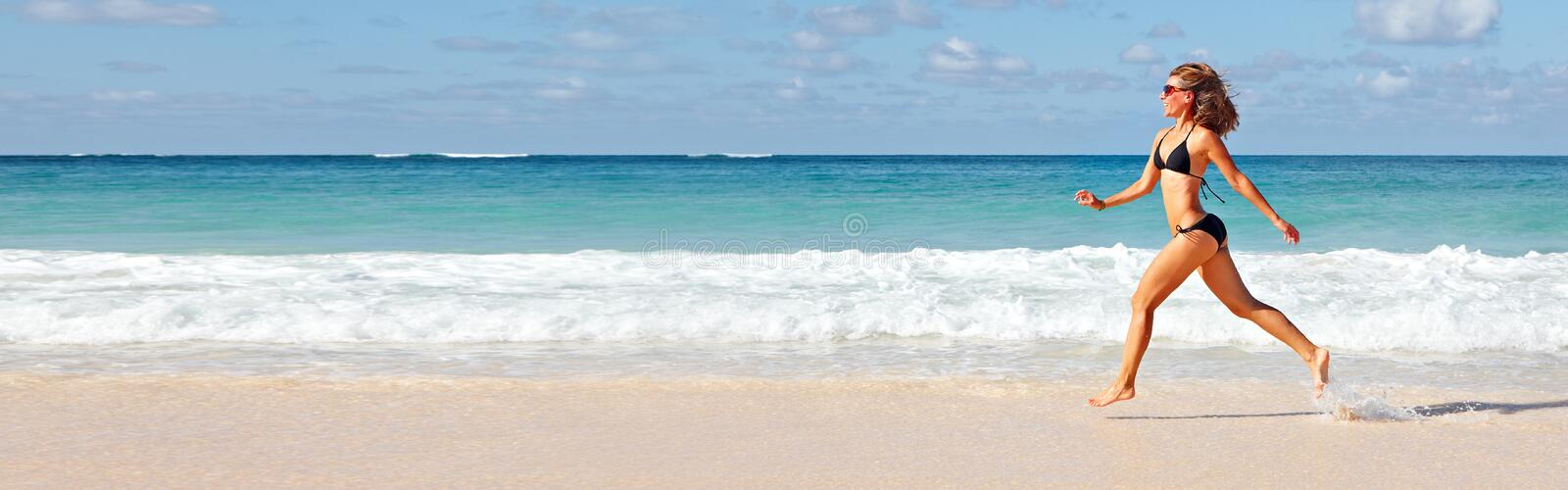 Woman running on the beach stock photo