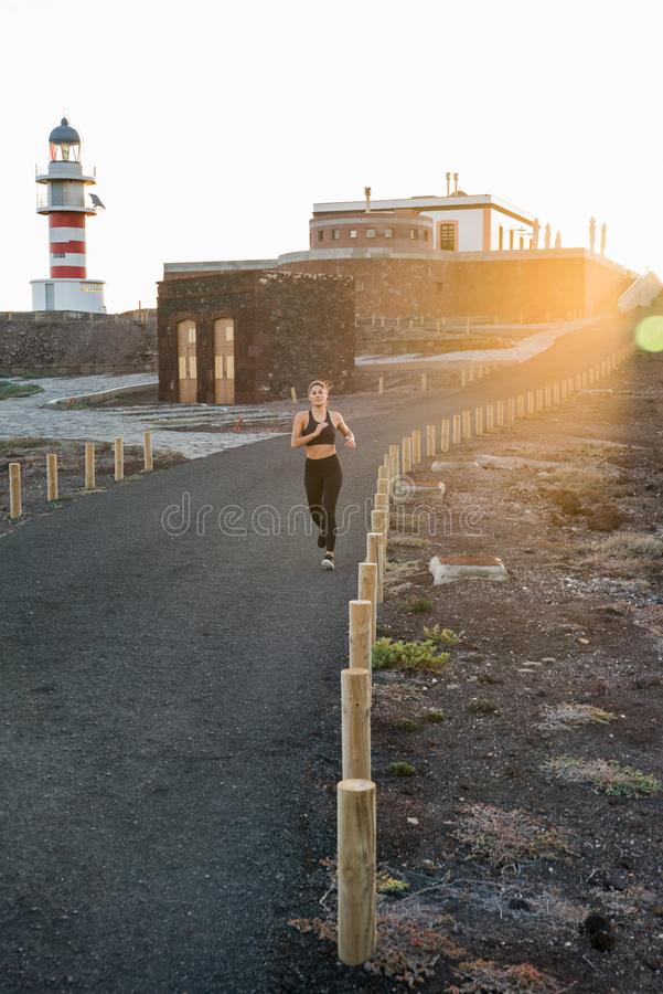 Woman running on a black tarred road with poles. Woman running in the distance on a black tarred road with low poles marking the path in the sunset stock image