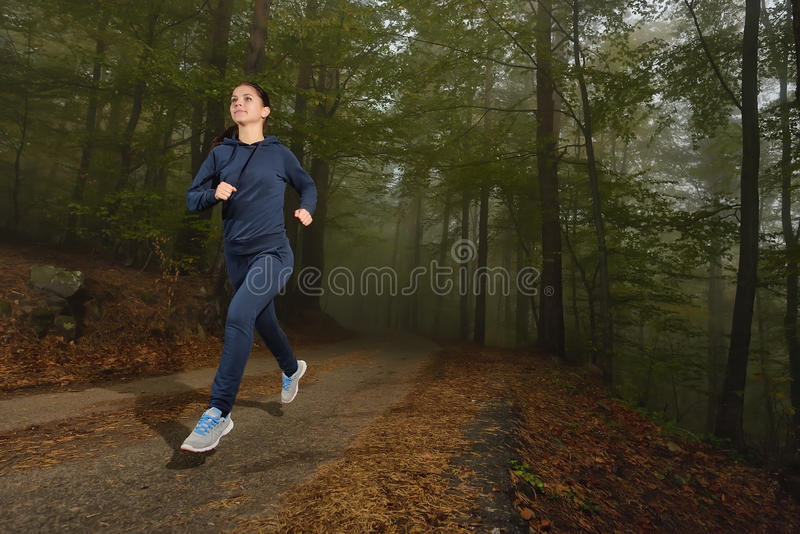 Woman running in forest area, training and exercising for trail run marathon endurance royalty free stock photo