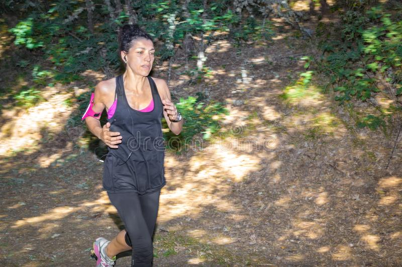 Woman running at forest trail in sunrise light. royalty free stock images