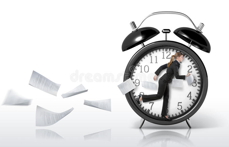 Woman running in a giant clock stock photography