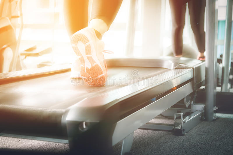 Woman running in a gym on a treadmill concept for exercising, fitness and healthy lifestyle stock photo