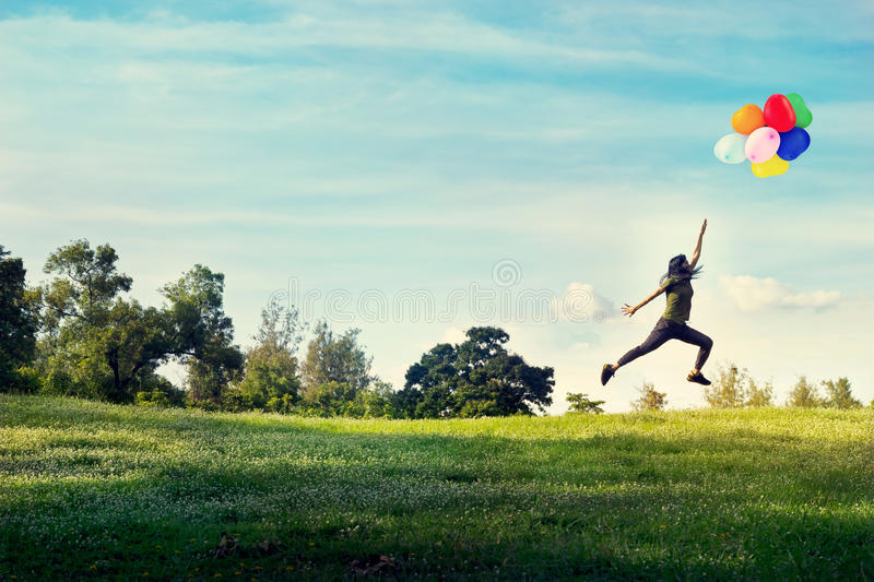Woman running and jumping touch balloons floating in the sky on green grass and flower field stock images