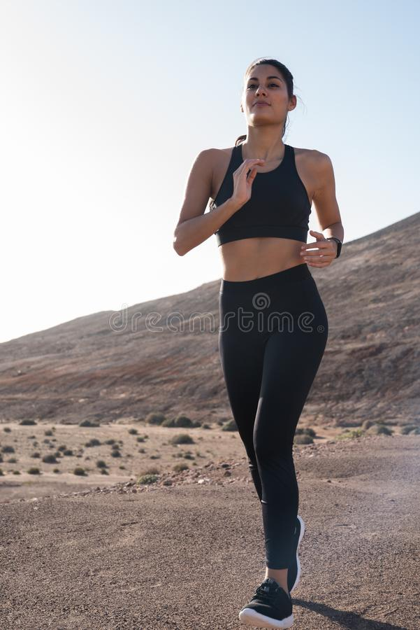 Woman running next to a grass verge in the desert. With the mountains in the background royalty free stock photography