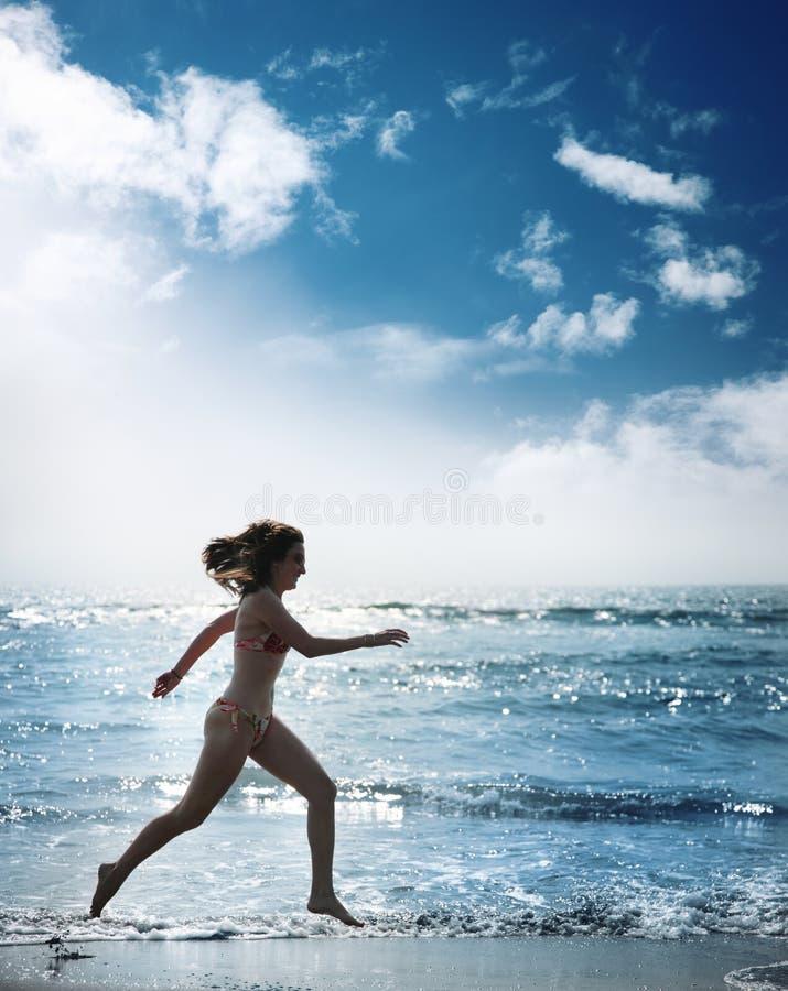 Woman running ocean. Woman running along beautifil ocean stock photography