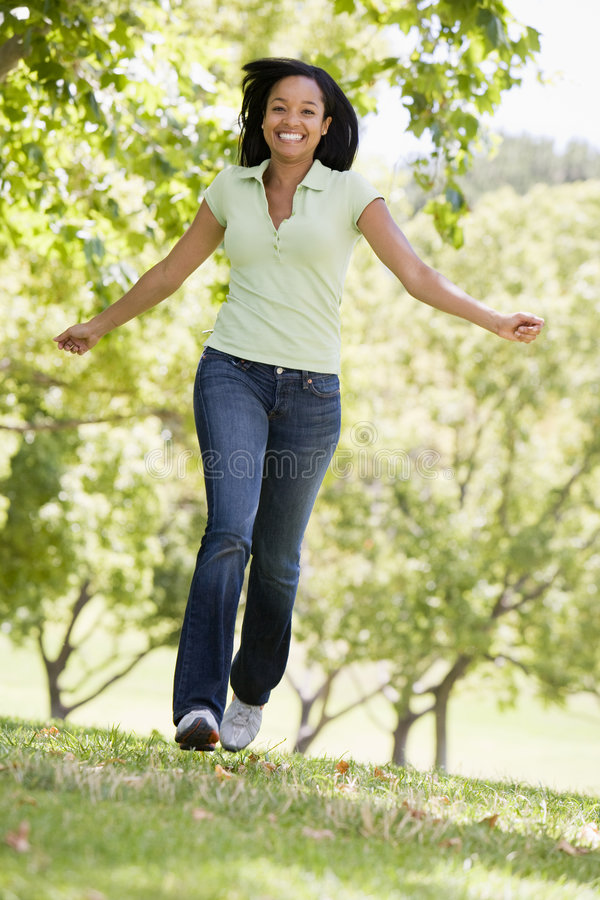 Woman running outdoors smiling stock image
