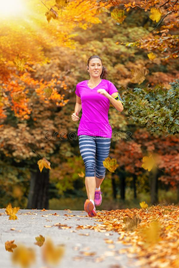 Woman running in a park during autumn time stock images
