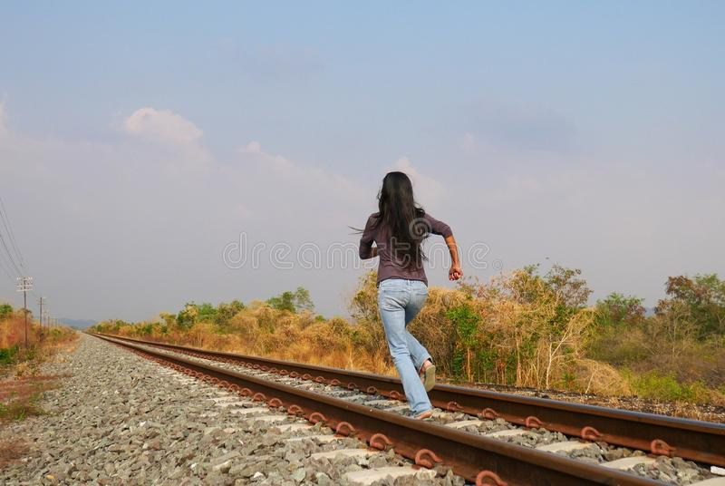 Woman running on railway, need to escape. Woman running on railway, run away, need to escape, going far, towards the unknown, best way to relax, to decompress royalty free stock images