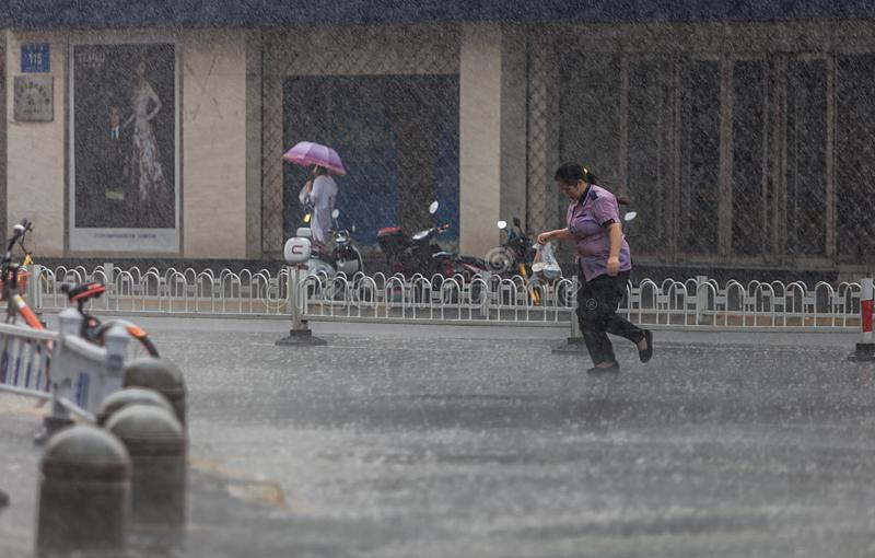 Woman running in the rain. On July 29, 2018, a sudden downpour in Nanjing, China, a woman running a box lunch in the rain
