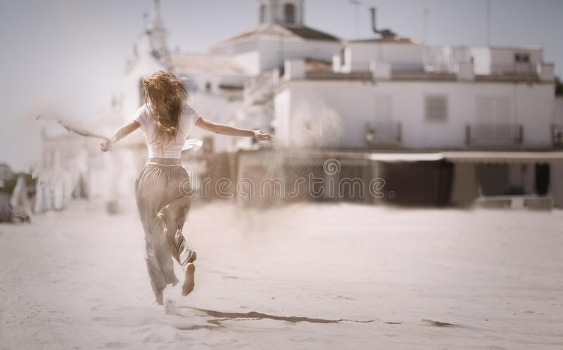 Woman Running on Sand Near White Concrete Building royalty free stock photo