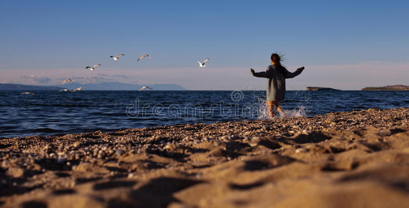 Woman running on sandy beach royalty free stock photography