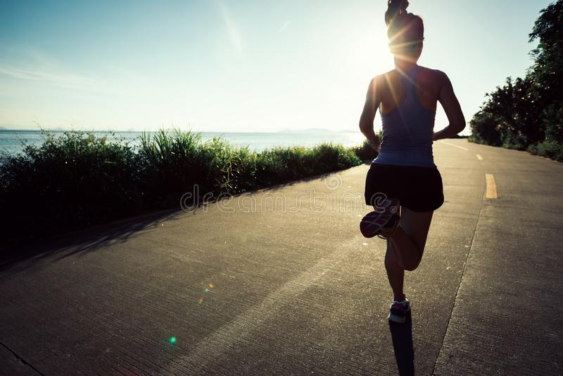Woman running on seaside trail stock photo