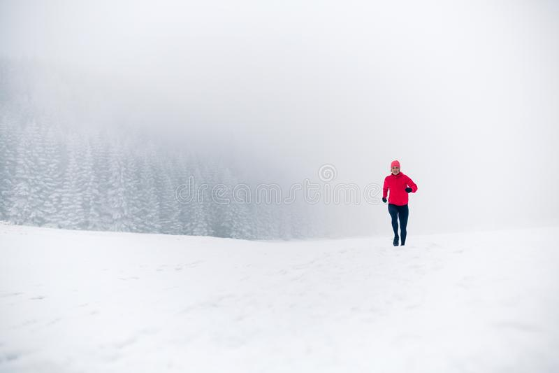 Woman running on snow in winter mountains stock photos