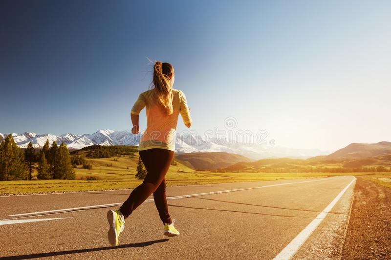 Woman running straight road mountains outdoors royalty free stock photo