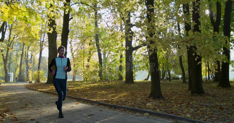 Woman Running in the Sunny City Park. Morning Light. Woman Running in the Sunny City Park. Morning Light royalty free stock images