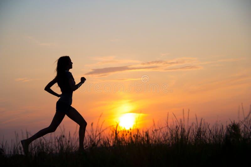 Woman running at sunset stock photos
