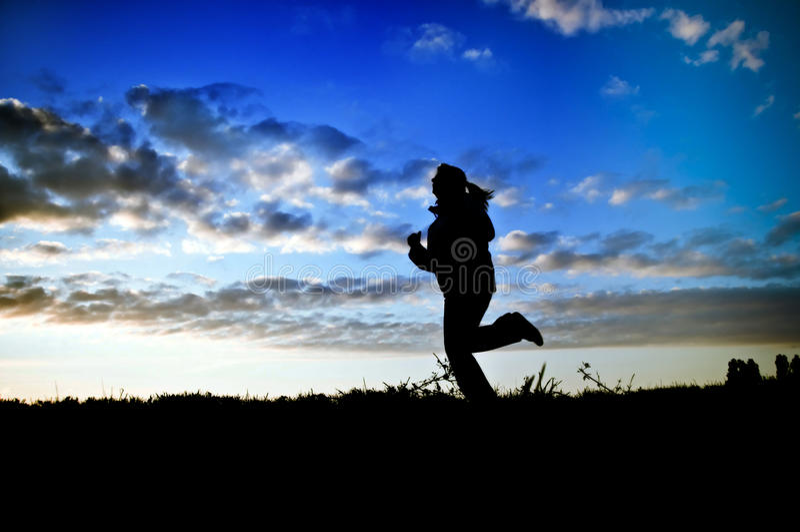 Woman running at sunset royalty free stock photo