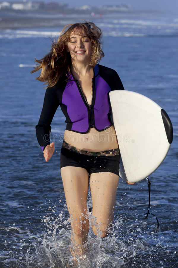 Woman running with surfboard stock photography