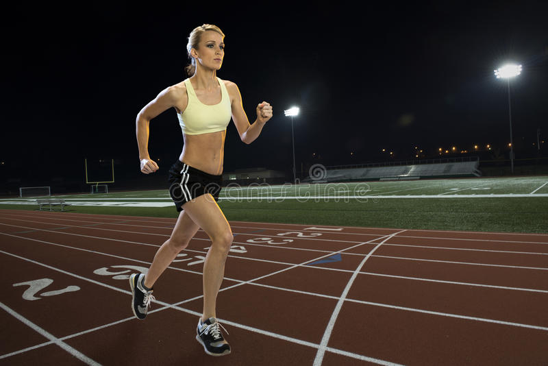 Woman running on a track. At night stock photos