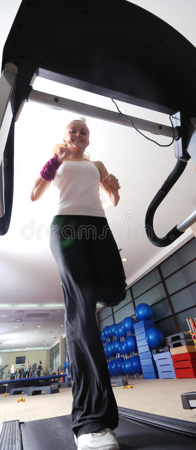 Woman running on treadmill stock image