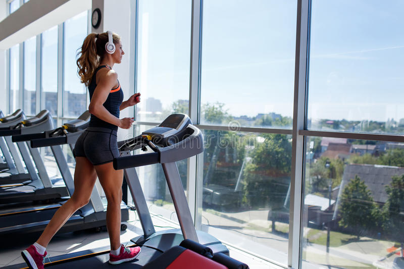 Woman running on treadmill and listening to music royalty free stock photo