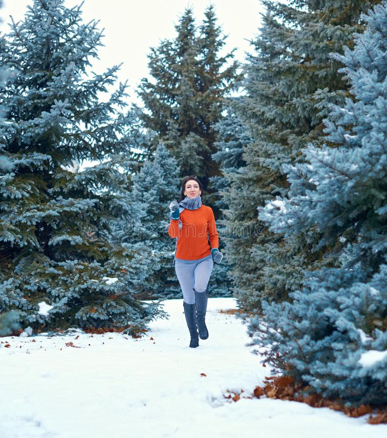 Woman is running in winter forest, beautiful landscape with snowy fir trees royalty free stock photos