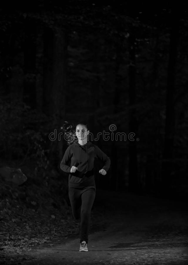 Woman running in wooded forest area, training and exercising for trail run marathon endurance royalty free stock photography