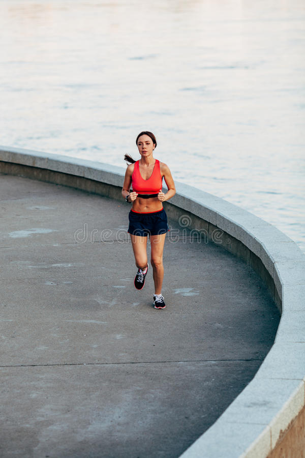 Woman runnning along granite curved parapet royalty free stock image