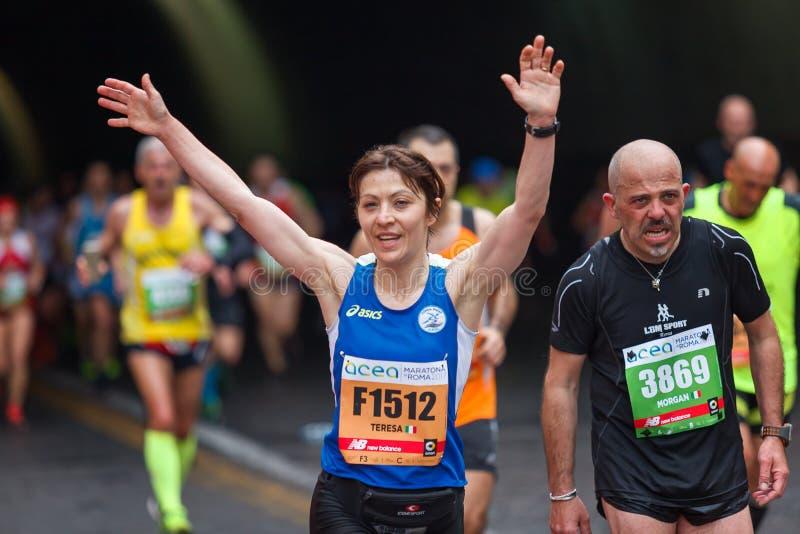 Woman runs marathon, arms raised, victory sign royalty free stock photography