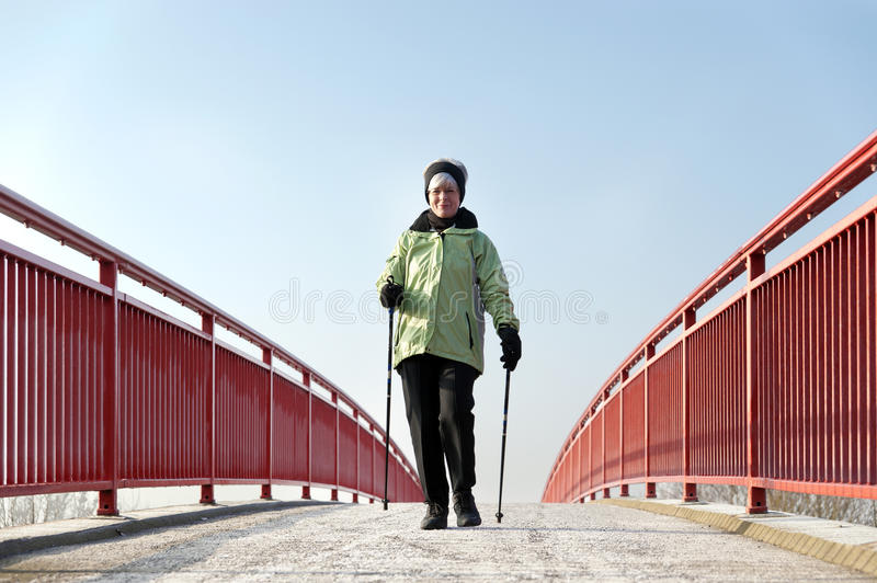 Woman runs over a bridge. Woman running during Nordic Walking over a bridge with red railings stock image