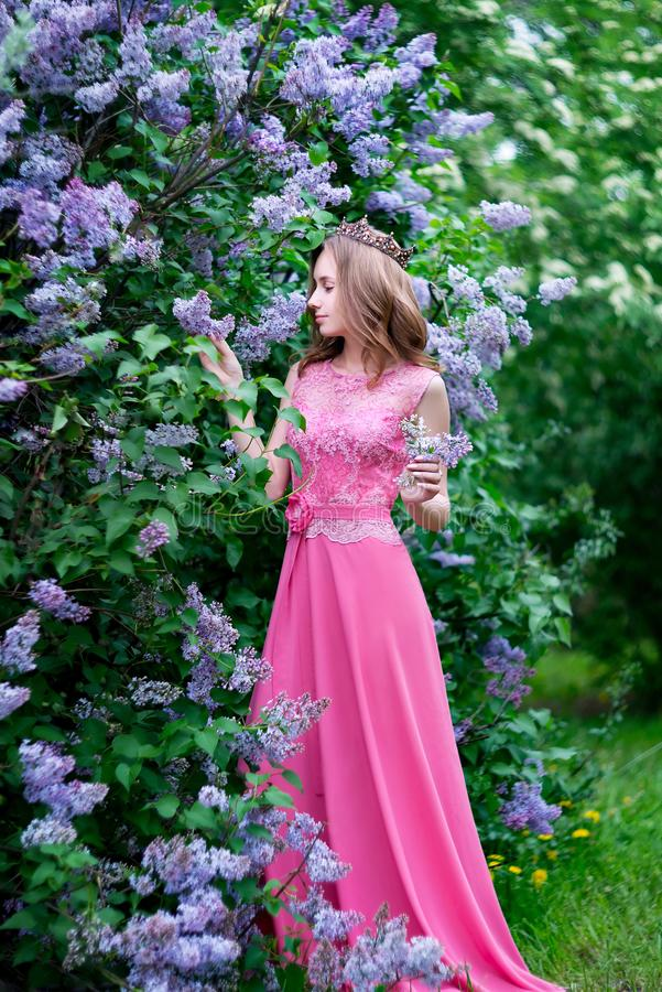 Woman, russian model in bloom spring lilac park. Woman, russian model in spring lilac park royalty free stock image