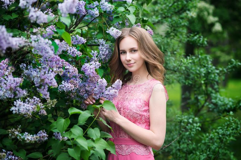 Woman, russian model in blossom spring lilac park. Woman, russian model in spring lilac park royalty free stock image