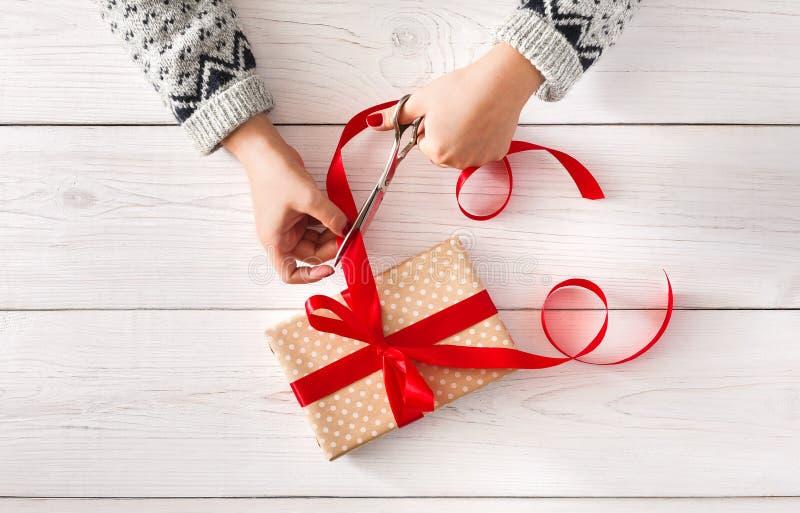 Woman& x27; s übergibt die Verpackung des Weihnachtsfeiertagsgeschenk iwith Rotbandes lizenzfreie stockfotos