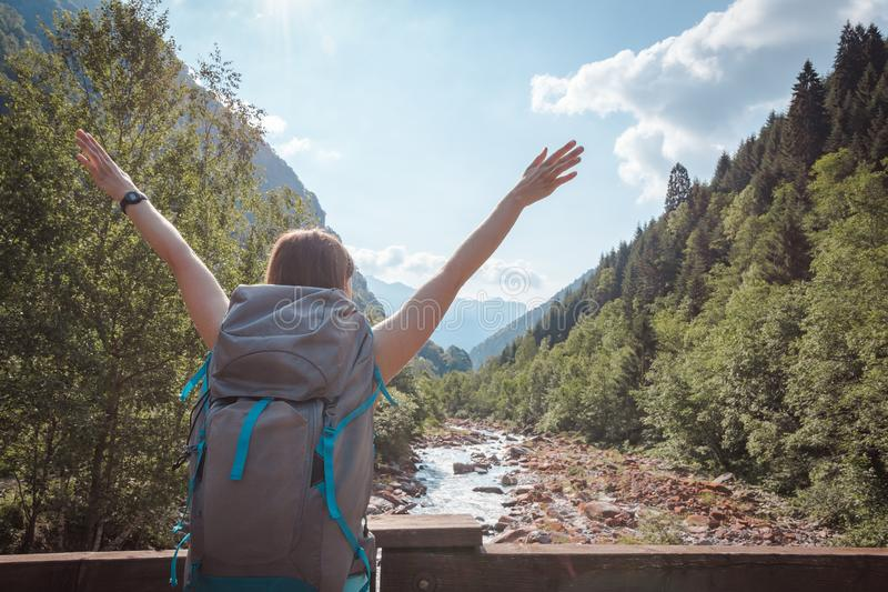 Woman`s arms raised on a bridge crossing a river surrounded by mountains stock images