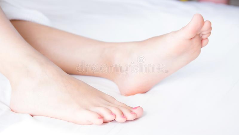 Woman`s bare feet on bed in light room.Beautiful and elegant female foot .Spa, scrub and foot care concept. royalty free stock images