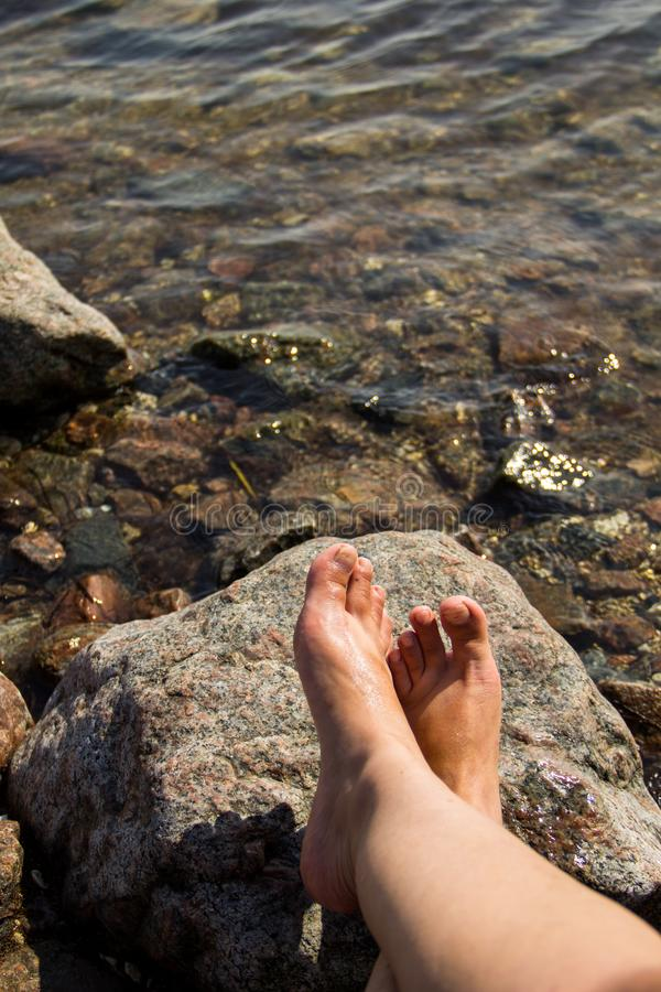 Woman`s bare feet near the sea on rock stock images