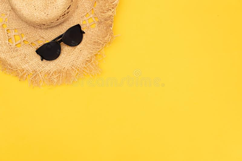 Woman`s beach accessories: rattan bag, straw hat, tropical palm leaves on yellow background. Summer background. Flat lay, top vie stock photo