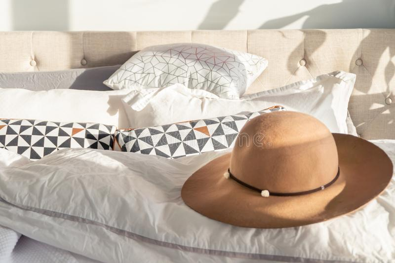 Woman`s beige sun hat with trim and wide brim on a fluffy bed, with sunlight shining indoors. Depicting holidays, relaxation and. Going out in fashion stock photos