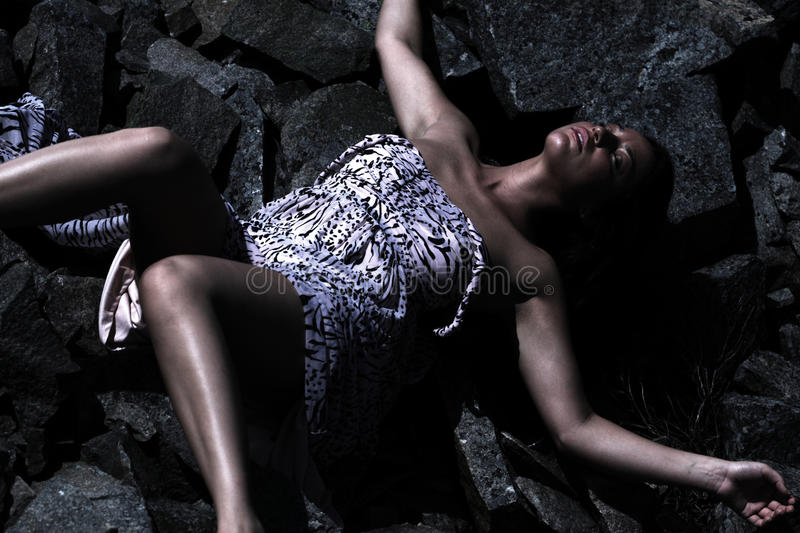 Woman's body fallen down. Young woman's body lying in an abandoned granite quarry stock image