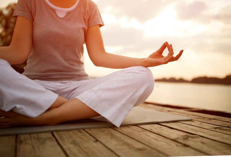 Woman in lotus pose practicing yoga, concept stock photography