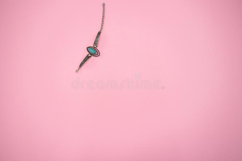 Woman`s bracelet with turquoise gemstone on pink background royalty free stock image