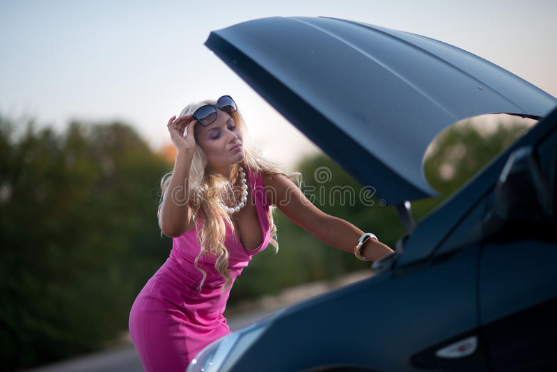 The woman's car broke down. Young attractive woman's car broke down on the road royalty free stock image
